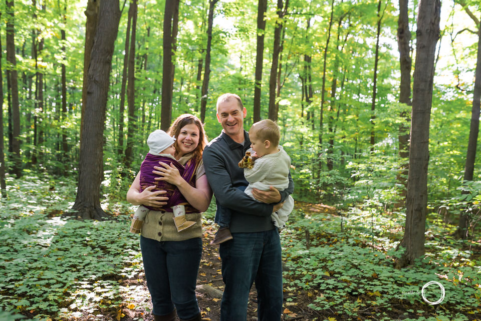 Newborn baby and her family in the forest with sunlight behind them with babywearing.