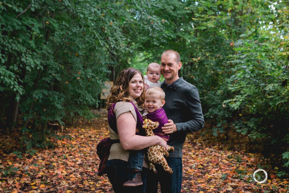 Family newborn photos in Ottawa with babywearing and a giraffe.