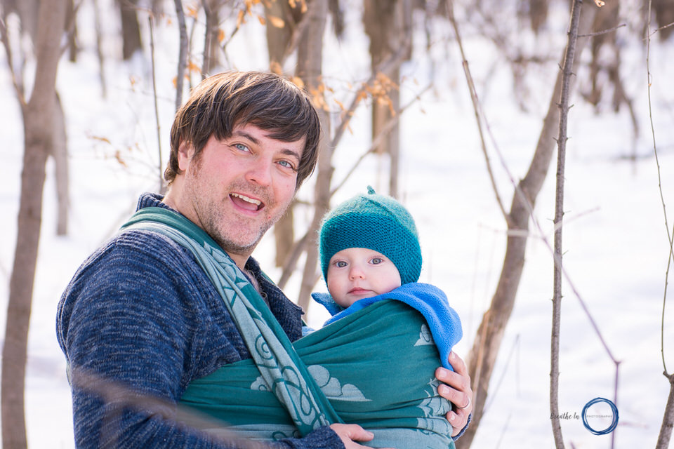Dad smiling with son during babywearing photo session.