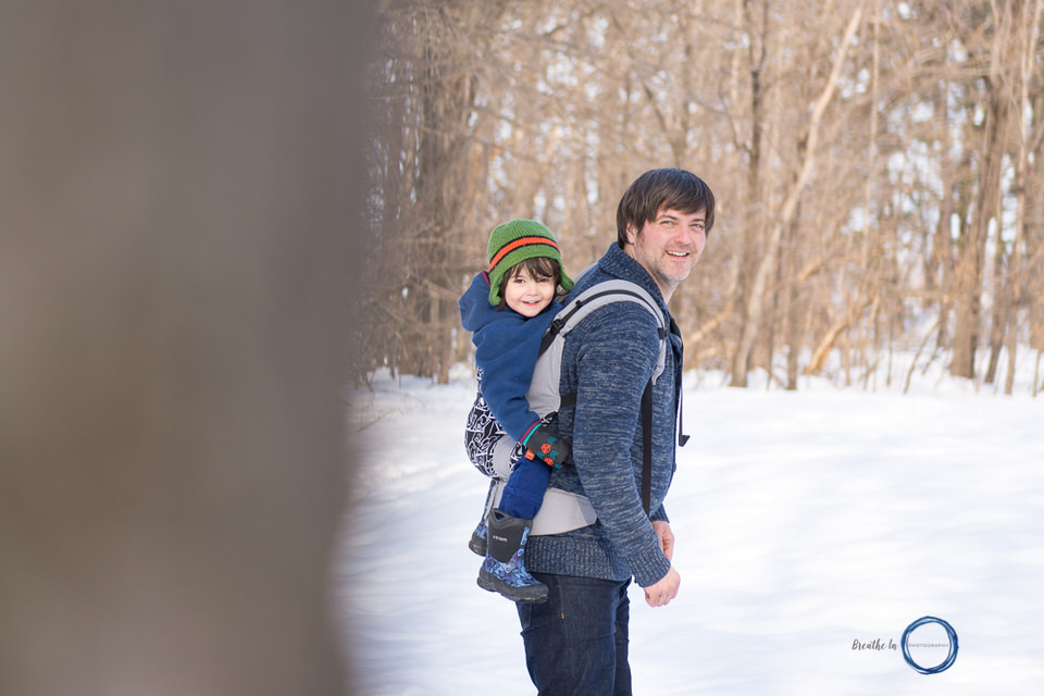 Dad carrying toddler son in Tula at Vanier Sugar Bush in Ottawa.