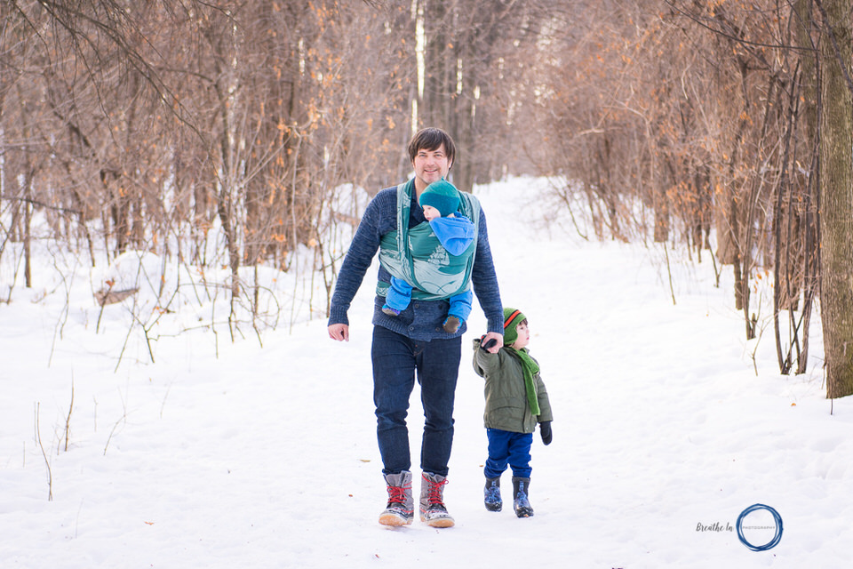 Dad carrying his baby in wrap and holding toddler's hand in winter.