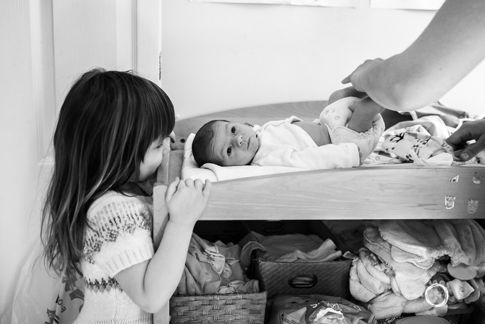 Big sister watches her newborn brother get his diaper changed.