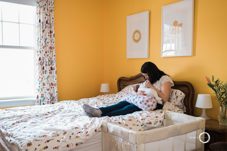 Mom breastfeeding new baby at home on bed in yellow room.