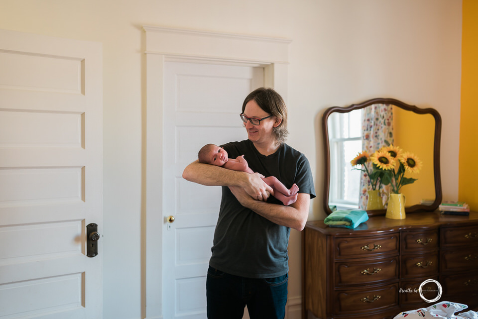 Dad holding baby son at home.