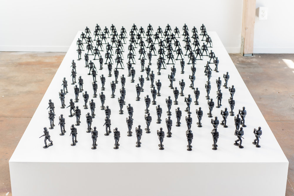 "Installation View. Wooden platform with toy soldiers (4""), aerosol paint."