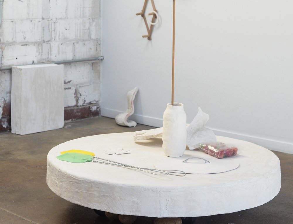 Rebeca Bollinger, Still Life with Fly Swatters and Holes, 2015.   Glazed and unglazed ceramic and porcelain, acrylic, spray paint, flashe, wood clothespins, plastic bags, photographs, brass knob, screws, wall rack, door number, foam, plaster, shims, wood, casters, potatoes, acorns, fly swatters, cardboard, porcelain with silver handle, artificial strawberries, gaffers tape.   Size variable.