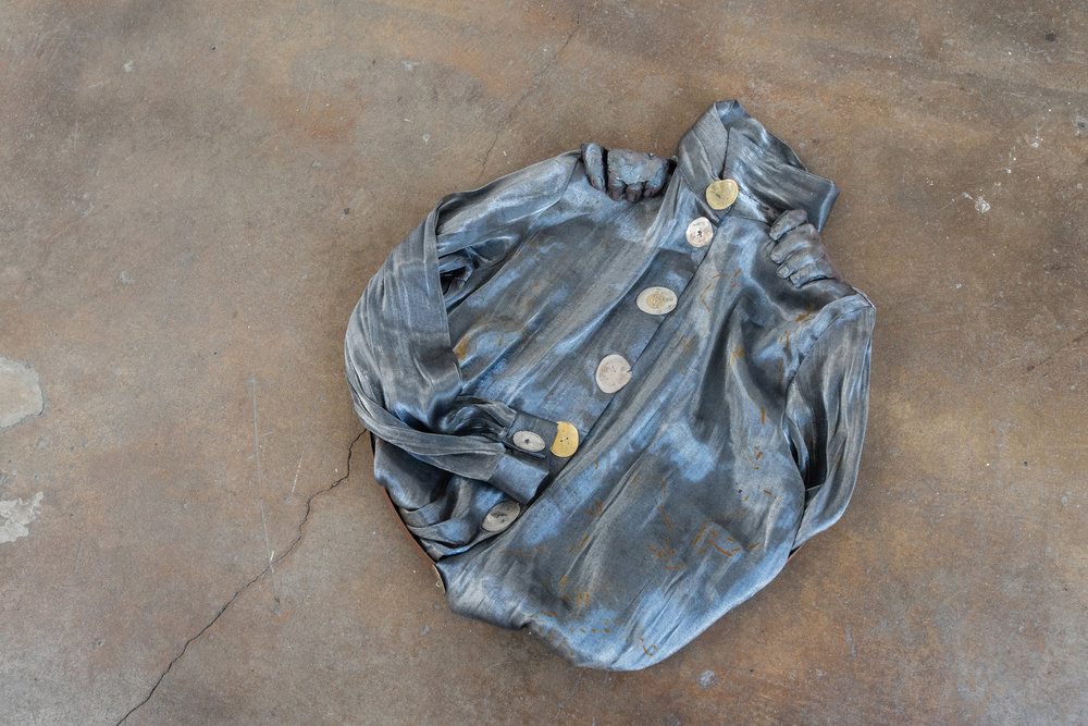 Jenine Marsh,  contortion (steel) , 2018. Found metal ring, rust-stained blouse, train-flattened and drilled coins of mixed currencies, wire, gypsum cement, powdered pigment.