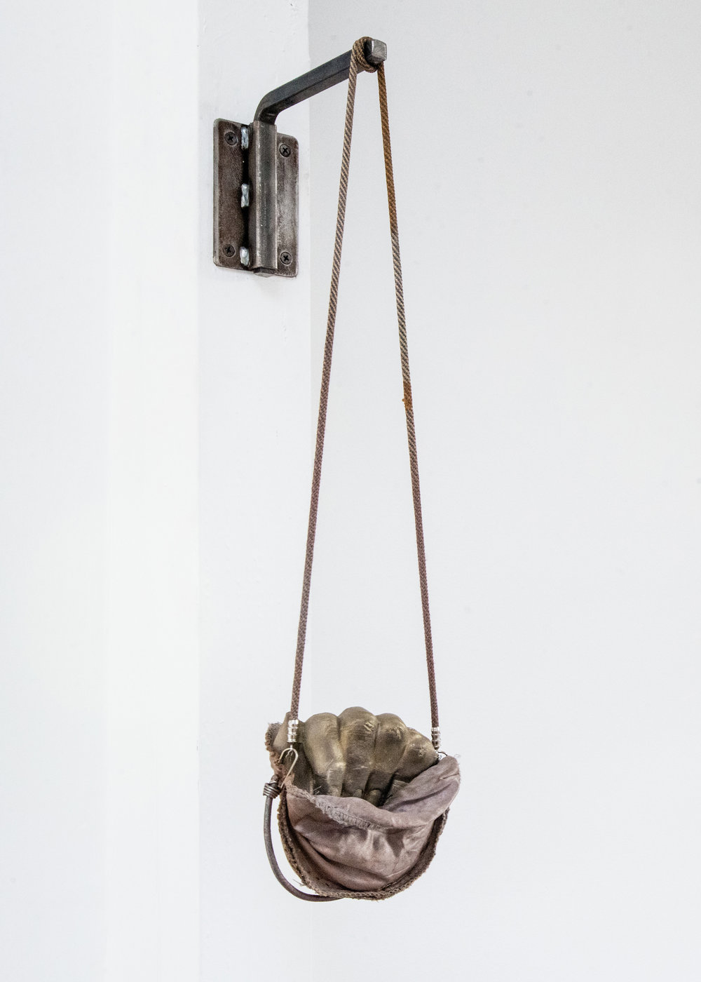 Jenine Marsh,  fist in pocket , 2018. Rust-stained shoulder-pads, necklace cord, bungee cord, staples, wire, powdered pigment, gypsum cement, steel hardware.