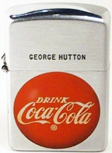 "This is a unique Town & Country 1951 Zippo with the red button logo ""Drink Coca-Cola"" introduced in 1947 hand engraved by George Hutton, an employee of Zippo Mfg. Co ."