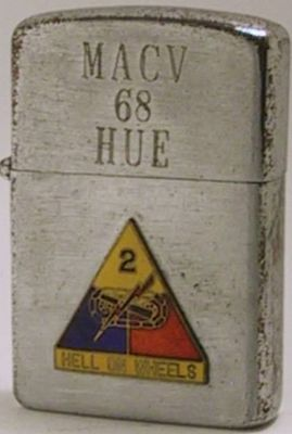 "This is a Universe Lighter with the engravings ""MACV 68 Hue"".  The Military Assistance Command Vietnam had quarters in Hue.  The attached badge is that of the 2nd Armored Division of the Army nicknamed Hell on Wheels"