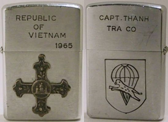 "1958 Zippo with an attached Catholic cross badge and ""Republic of Vietnam - 1965"" engraved on the lid. The reverse case is engraved with a parachute and leopard logo, while the lidis engraved with ""Capt. Thanh Tra Co"""