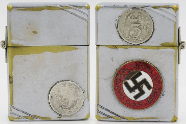 1934-36 Zippo with repaired outside hinge.  The front has an attached English 3 pence coin as does the reverse lid with the 3p coin dated 1920.  The reverse case has a German Nazi pin attached.  Both the lighter and the attached coins and badge show signs of heavy use and one can only speculate as to whether the lighter was once owned by an English Nazi sympathizer. or....?