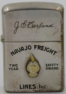 "1960's Sterling Silver Zippo advertising ""Navajo Freight Lines, Inc. Two Year Safety Award""  The lighter also is inscribed with  the name ""J.G. Carland"" and has an attached Indian head badge in gold"