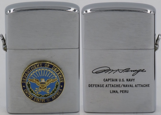 "c 1969 Cornet Rocky lighter with an attached US Department og Defense badge on the front and the signature of A. M. Savage (Arthur Mix) and ""Captain US Navy Defense Attache/Naval Attache Lima Peru"" on the reverse"