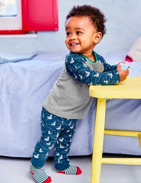Baby in Boden pyjamas in a nursery with Seascape wallpaper