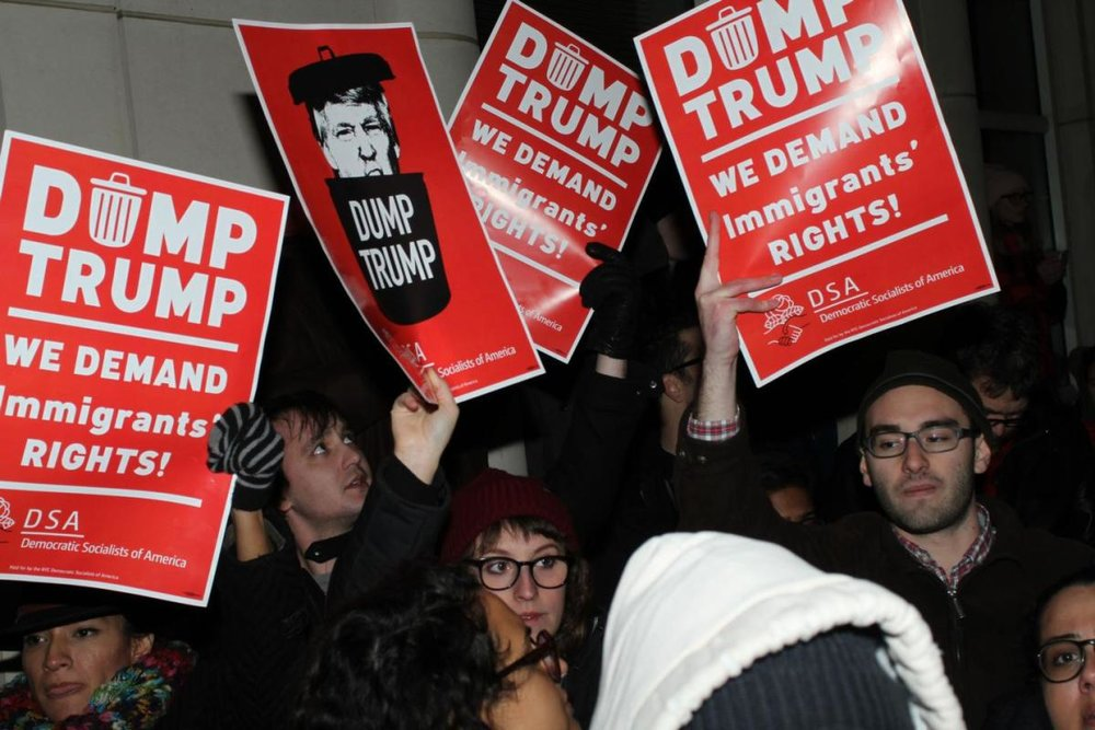 Funded by Soros, covered by our national press, Democrat Socialists of America are at kennedy with pre-printed signs within hours of Trump's imposition of a no-fly list