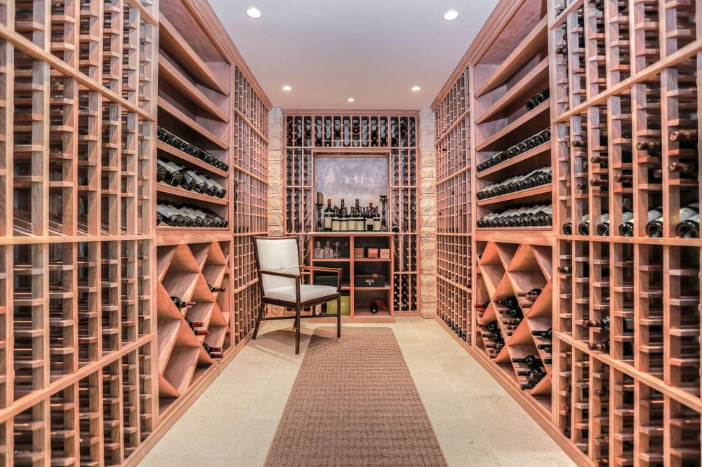 look! A wine cellar with more than a dozen bottles in it; eventually, builders will figure out that no one uses home theatres, wine cellars or whirlpool tubs, and will put the space to BETTEr, or at least fifferent use. Eventually.