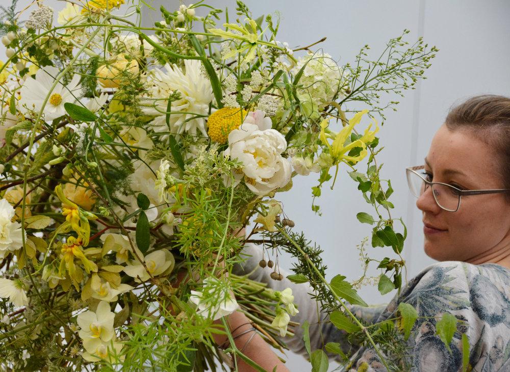 Birgit Haberschrick, Graz/A: In voller Aktion während dem Binden ihres Meisterstrausses. Sie gestaltete eine luftig-lockere Ellipsenform, womit ihr Strauss symbiotisch mit der ovalen Messingschale verschmolz, welche seit über 150 Jahren in Familienbesitz ist.