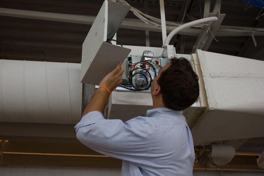 Staff_OES_Comm_Fitzgerald_Examining Ceiling HVAC Box - Landscape.jpg