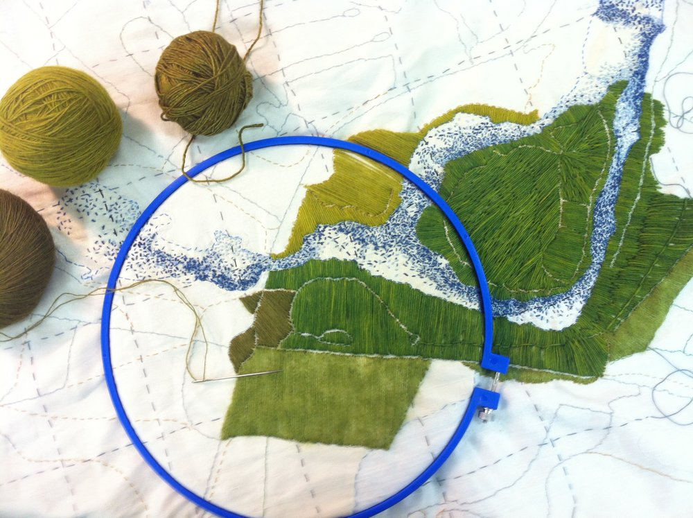 Work in progress in the Montreal studio, a detail of my map of Blönduós, stitches suggesting the dancing light on the blue River Blanda and the vivid green of Hrútey Island, to the right of the embroidery hoop. September 2016.
