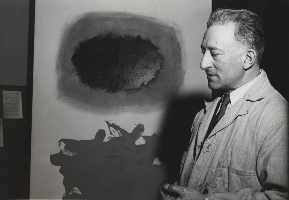 Adolph Gottlieb before one <br>of his own works <br>1958
