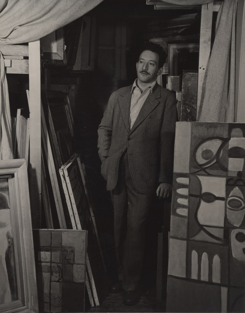 Adolph Gottlieb with his works <br>c. 1942<br>Photo by Aaorn Siskind <br>© Aaron Siskind Foundation