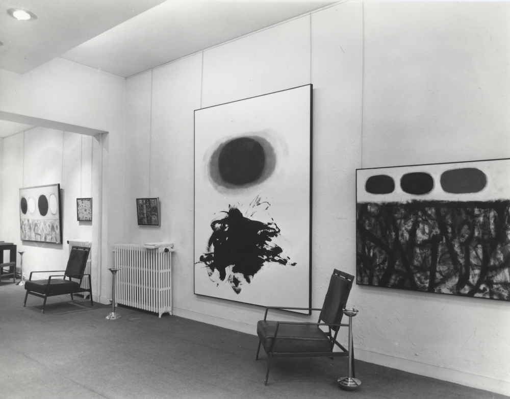 """Installation view of """"Gottlieb: Ecole de New York"""" at Galerie Rive Droite, 1959. Crimson Spinning (1959) is shown at center."""