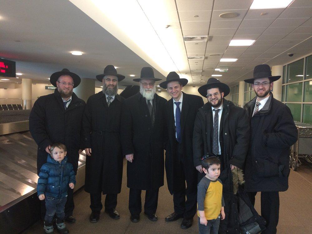 Welcoming the Birons at MSP Airport From Left: Rabbi Yossi Lowinger (with Yaakov) Rabbi Yechezkel Greenberg, HaRav Chaim S. Gibber, Me (with Elya), Rabbi Adam Crystal