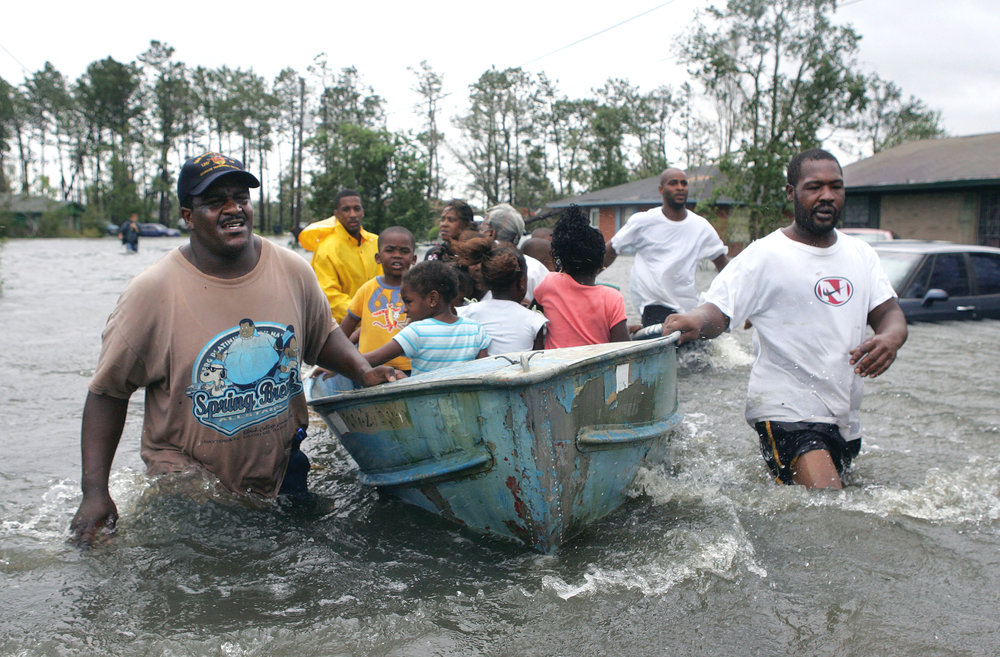 Rescuers use an old row boat to evacuate children and an elderly woman from their flooded homes in Gulfport, Miss., after Hurricane Katrina struck the Gulf Coast Monday, Aug. 29, 2005. ASSOCIATED PRESS.