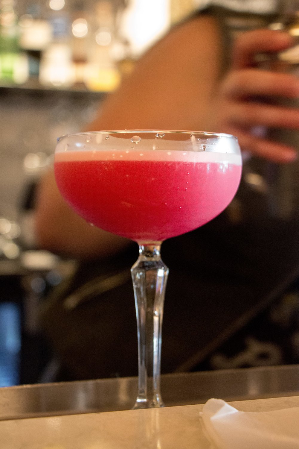 WIND SHADOW FIZZ: Elderberry simple syrup, egg white, gin, and lemon juice