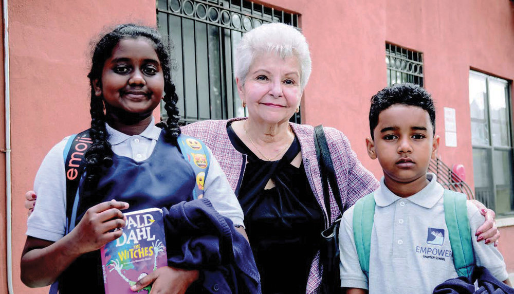 Maria Rosado (with two neighborhood school children) efforts in affordable housing will be recognized at this year's celebration. She is in front of one of her buildings at 2187 Strauss Street in Brownsville.