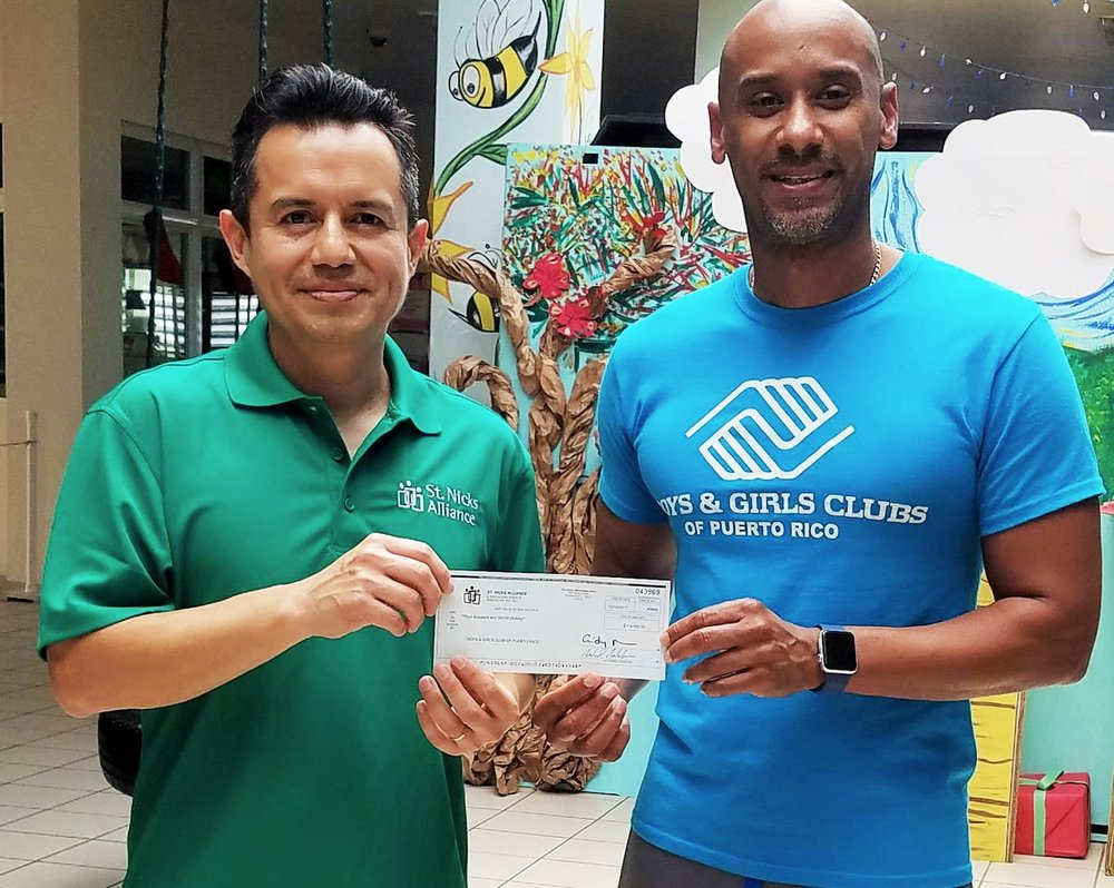 José Leon, Dep. Executive Director of St. Nicks Alliance, left, presents Noel Soler, Director, Boys and Girls Club of Puerto Rico in Isabela, Puerto Rico, with the $4,000 St. Nicks Alliance raised from their StNicksAllianceforPuertoRico.org campaign