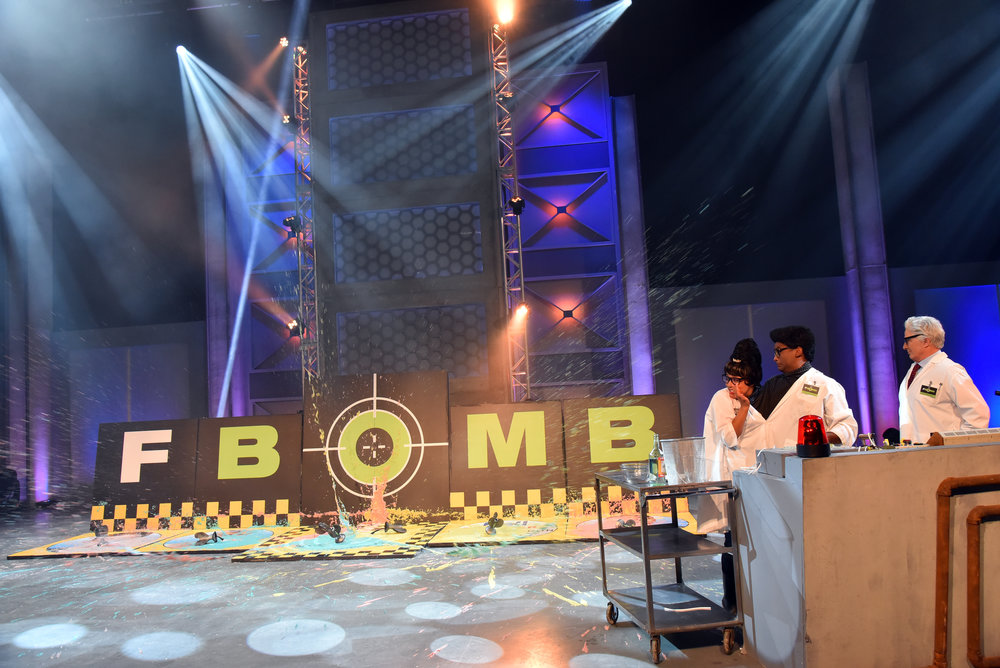 Watch out, Felicia and Fernando Mossenccop (Aisha Alfa, Darryl Hinds) and Dr. Von Rikkengord (Don Ferguson)! There's some major splashback from this year's F-Bomb Target of the Year.