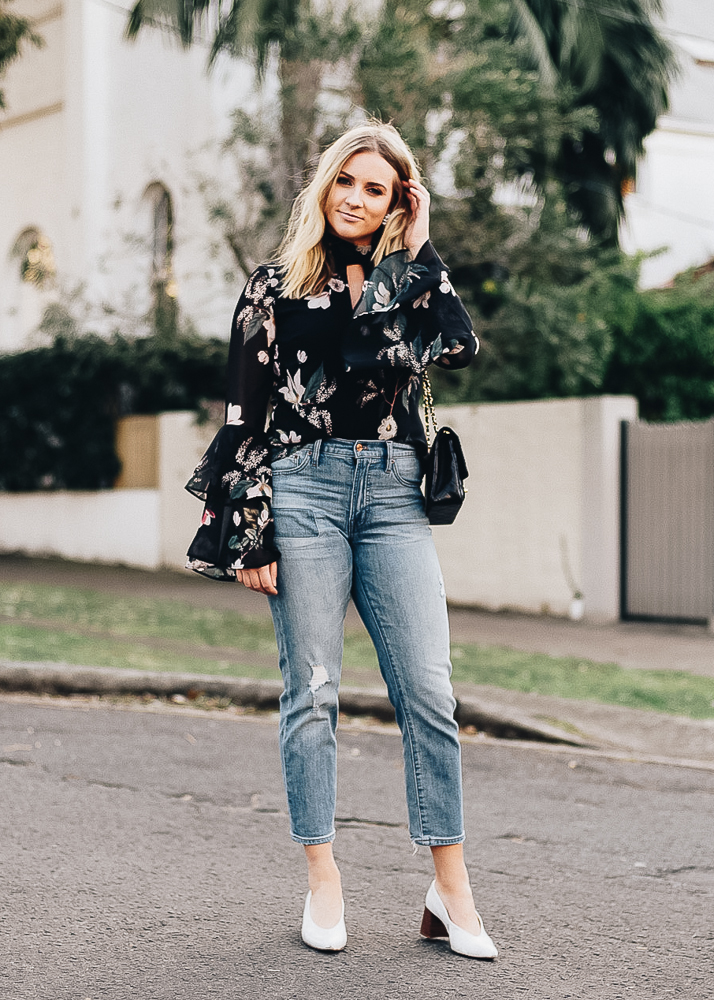 Christina Roys has on a beautiful bell sleeve floral top with classic denim jeans
