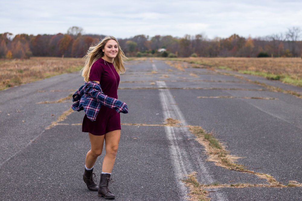 Dancing along the airstrip in a burgundy t-shirt dress