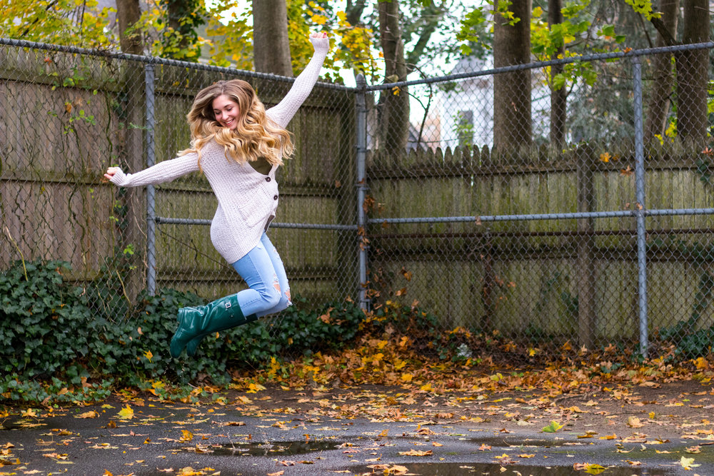 Jumping for joy with a green women's outfit