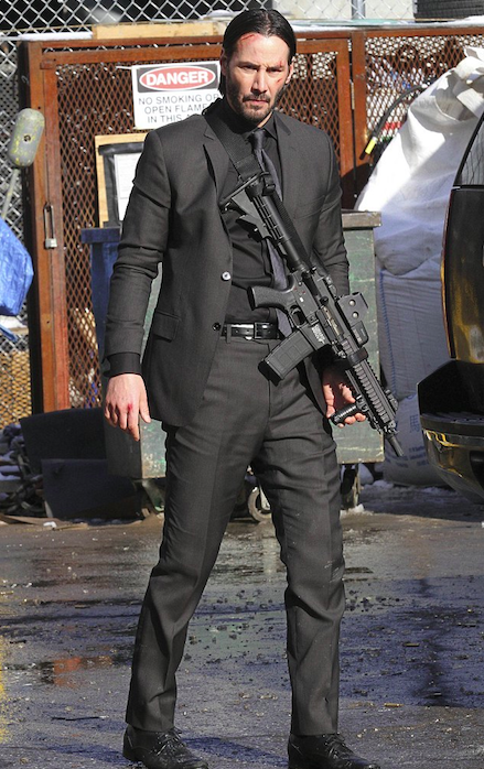 John Wick wears both black and charcoal suits that feature both slim notch and regular notch lapels with monochromatic clothing underneath.