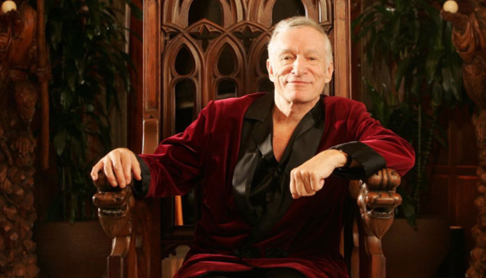 Hugh Hefner in his iconic burgundy velvet smoking jacket with black satin shawl lapels.