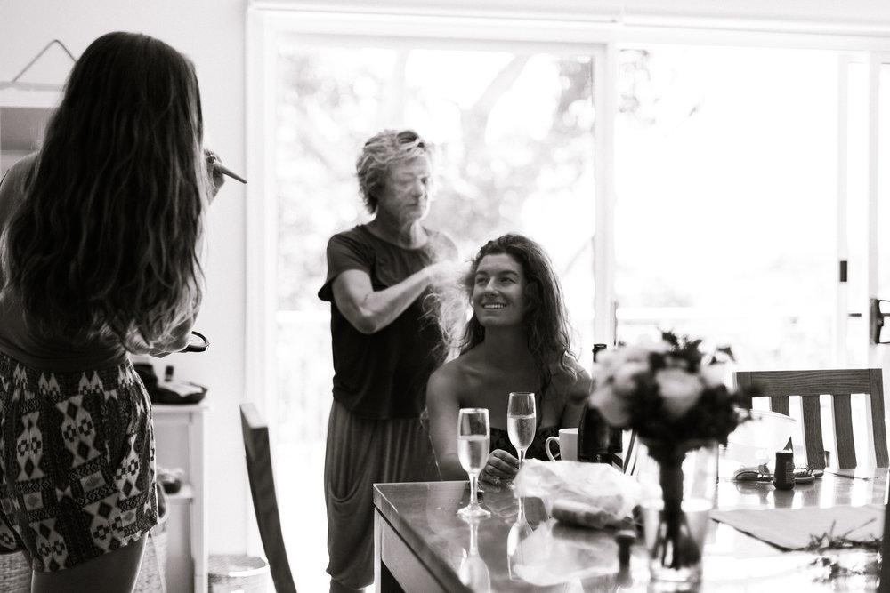 Bride Getting ready shot, with makeup artist and hairdresser o her wedding