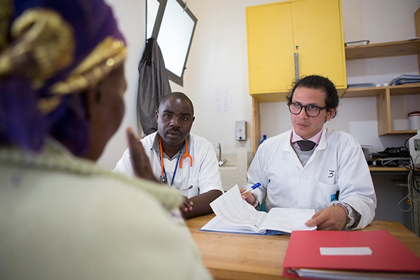 Dr. Kurt Figueroa (right) and Nurse Sebishyimbo François (left) see patients for their oncology consultations at Butaro District Hospital in Rwanda. Photo by Zacharias Abubeker for UGHE