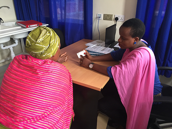 Study Coordinator Alphonsine Imanishimwe counsels a new patient through her first dose of medication. Photo by Neil Gupta