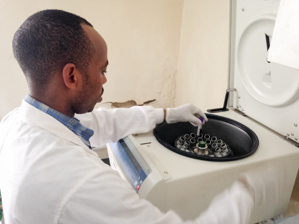 J.M.V. Halleluia, a laboratory technician working on Rwanda's hepatitis C study, places samples for laboratory testing into a centrifuge.