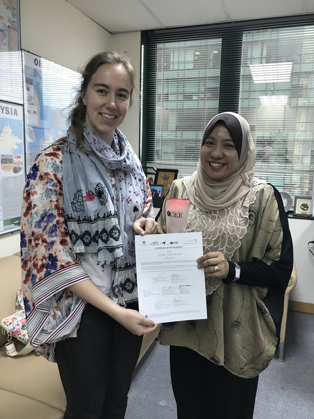 Presenting the certificate of participation to a practicing engineer participant in Kuala Lumpur.