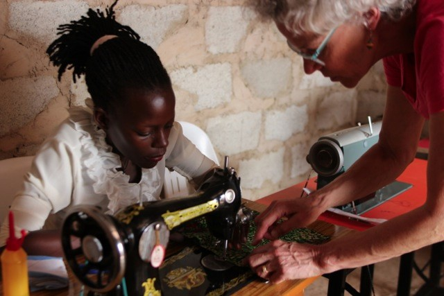 TEACHING, LEARNING  – Ellie von Wellsheim instructs Gorette in sewing a MoonCatcher pad carrier at Woman With a Purpose Sewing Guild in Wakiso, Uganda.