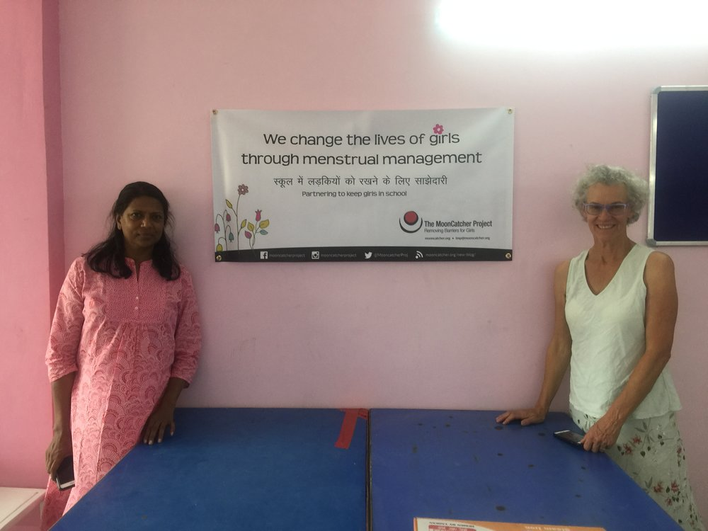 Ruchika and Ellie hang the MoonCatcher banner in our Delhi sewing center.