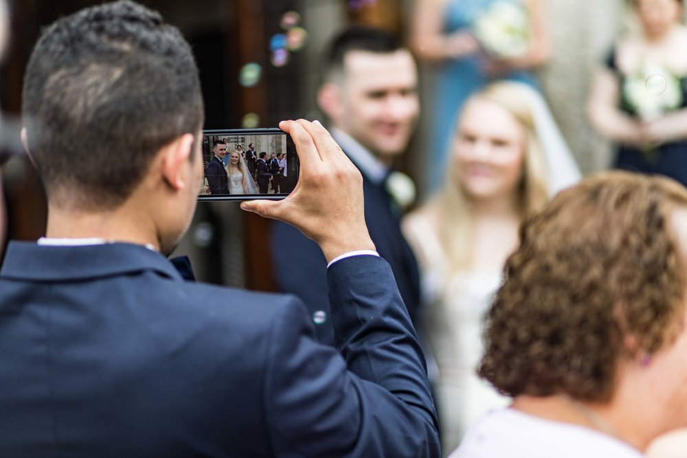 Groomsman taking iphone photo of bride and groom