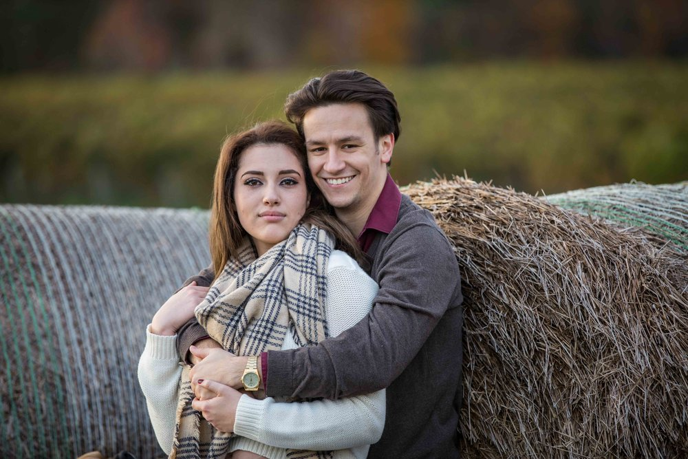 couple leaning on hay bale