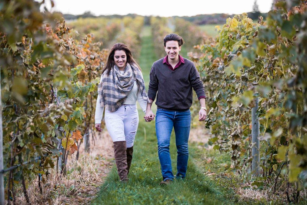 A couple walking through the vineyard holding hands
