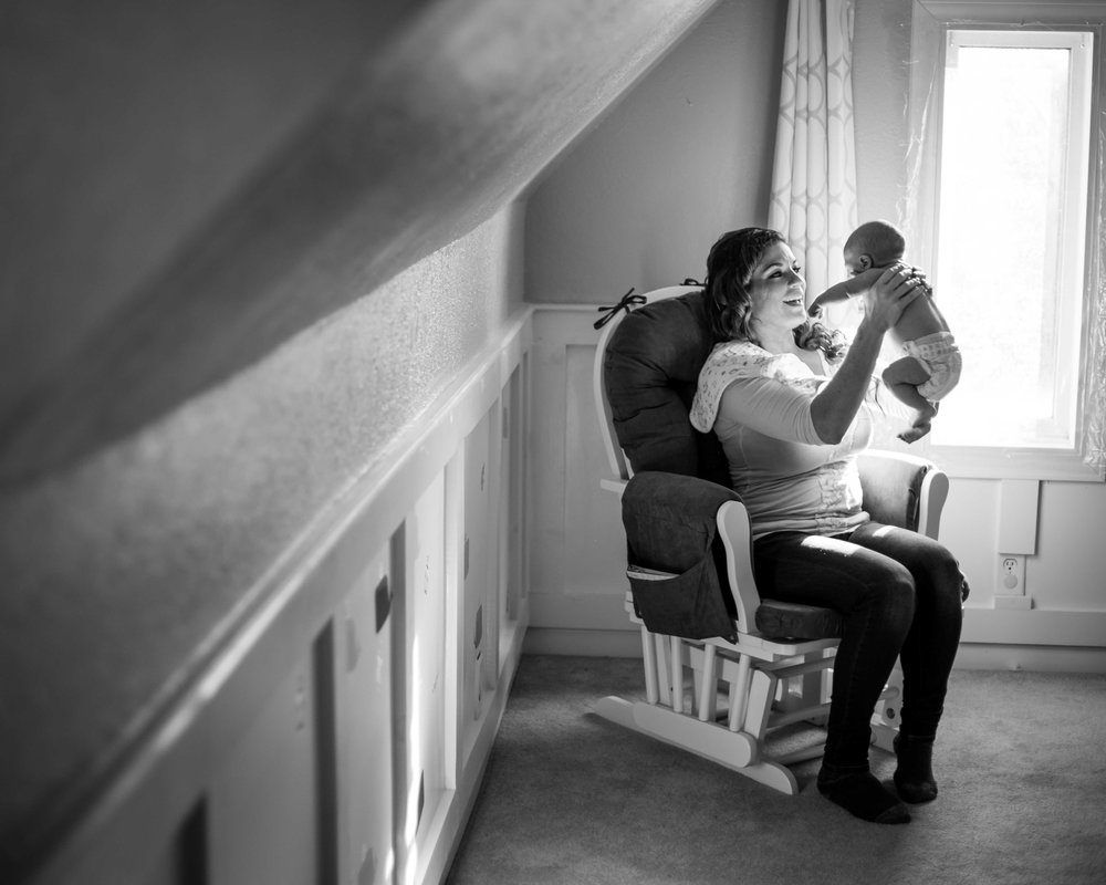 Mother holds her newborn up high while sitting in her nursing rocker