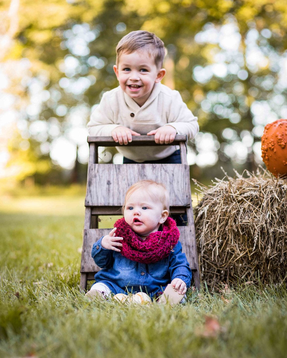 Siblings posing for a photo with a ladder, hay bales, and a pumpkin